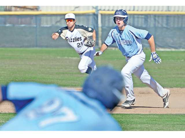 Golden Valley's Billy Fredrick (21) trails Saugus baserunner Caden Salkeld as he heads for third base on a hit during Wednesday's game at at Golden Valley High.