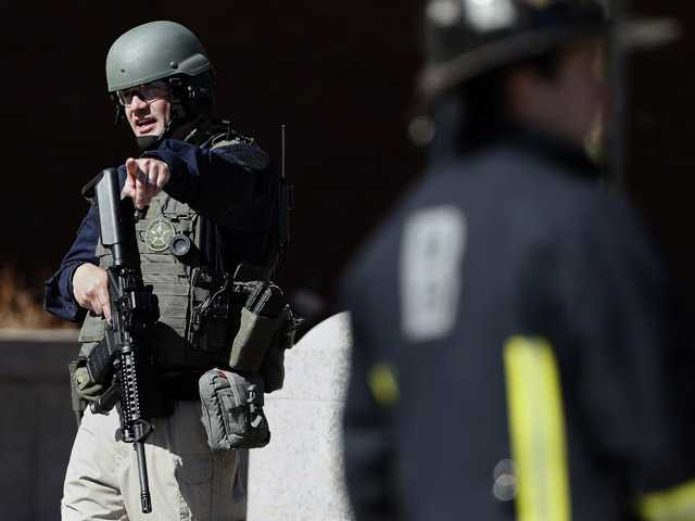 A heavily armed United States Marshall stands guard outside the Moakley Federal Court House in Boston after the building was evacuated on Wednesday.