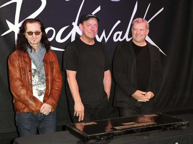 This Nov. 20, 2012 file photo shows members of the band Rush, from left, Geddy Lee, Neil Peart, and Alex Lifeson at the RockWalk induction of Rush at Guitar Center in Los Angeles.