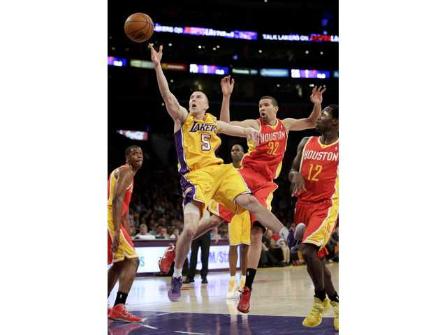 Los Angeles Lakers' Steve Blake, left, shoots against Houston Rockets' Francisco Garcia on Wednesday.