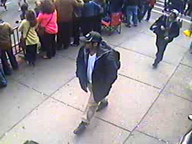 This surveillance photo provided by the FBI shows the two suspects, both in hats and carrying bags, walking among the marathon route in Boston before the explosions.