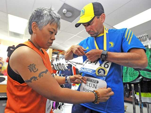 "Flo Mina, owner of the Runners Lane, places a bib on Dennis Lebman of Saugus before Thursday's ""Run For Boston."" Signal photo by Jonathan Pobre"