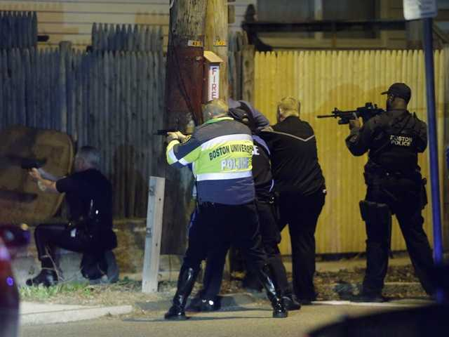 Police officers aim their weapons in Watertown, Mass. Friday.