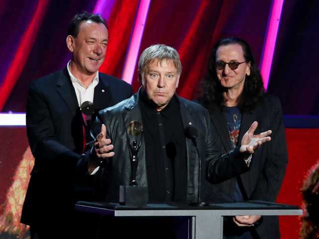 Alex Lifeson, center, Neil Peart, left, and Geddy Lee, of Rush accept their band's induction into the Rock and Roll Hall of Fame.