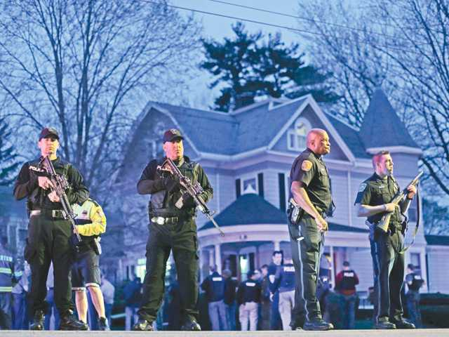 Police officers guard the entrance to Franklin Street, where a 19-year-old suspect in the Boston Marathon bombings was captured on Friday in Watertown, Mass., after a search that lasted all day.