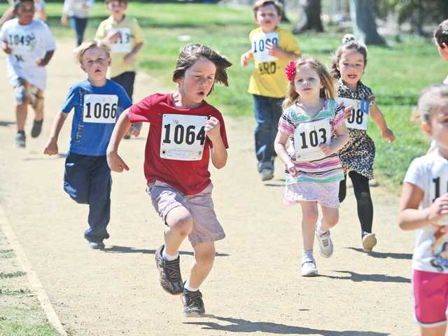 Luke Bergmann, 6, center, joins his 92 kindergarten classmates and 18 pre-schoolers as they participate in the jog-a-thon event to benefit the PTA at Rosedell Elementary School on Friday.