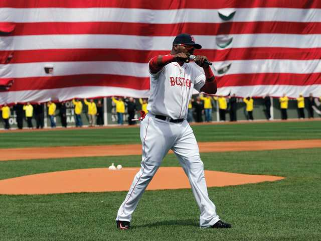 Boston Red Sox's David Ortiz pumps his fist in front of an Amarican flag and a line of Boston Marathon volunteers, background, after addressing the crowd before a baseball game between the Boston Red Sox and the Kansas City Royals in Boston on Saturday.