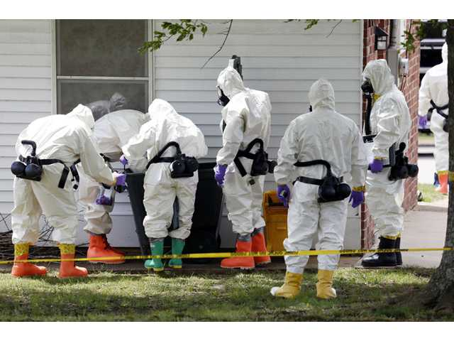 Federal agents wearing hazardous material suits and breathing apparatus inspect the trash can outside the West Hills Subdivision house of Paul Kevin Curtis in Corinth, Miss., on Friday.