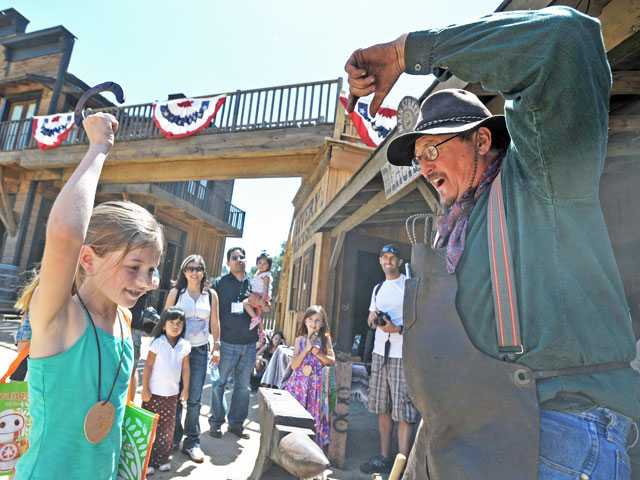 Maddie Haynes, left, of Stevenson Ranch, raises her new personalized lucky horseshoe created by blacksmith Mark Birdsall on Saturday at the Santa Clarita Cowboy Festival.