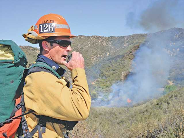 A Los Angeles County firefighter communicates to his crew as a small brush fire burns in Stevenson Ranch on Saturday afternoon.  The fire was out at 4:37 p.m.