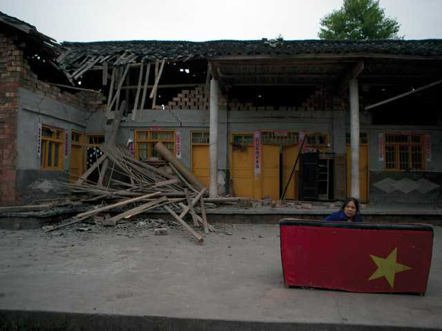 Zheng Xianlan, a 58-year-old corn farmer, awakens after spending the night sleeping on a sofa outside her house which was damaged by an earthquake near Shangli town in southwestern China's Sichuan province, Sunday. Residents awoke Sunday after spending the night outdoors or in their cars in the town near the epicenter of a powerful earthquake that struck the steep hills of China's southwestern Sichuan province, leaving at least 160 people dead and more than 6,700 injured.