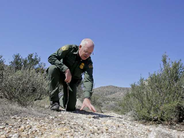 In this March 25, 2013 photo, Border Patrol agent Richard Gordon, a 23-year veteran of the agency, examines disrupted rocks along a path which tell him about the movements of human traffic where illegal immigrants enter the United States in the Boulevard area east of San Diego, in Boulevard, Calif.