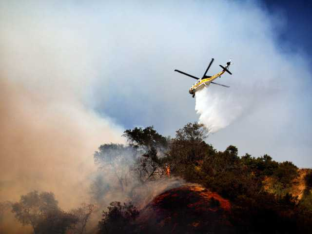 A helicopter drops water on a fire burning on a hilltop near homes on Saturday in Monrovia, Calif.