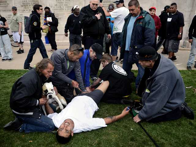 Denver Paramedics, Denver Police officers and good Samaritans tend to a shooting victim at Civic Center Park after the 4/20 pot rally Saturday in Denver.