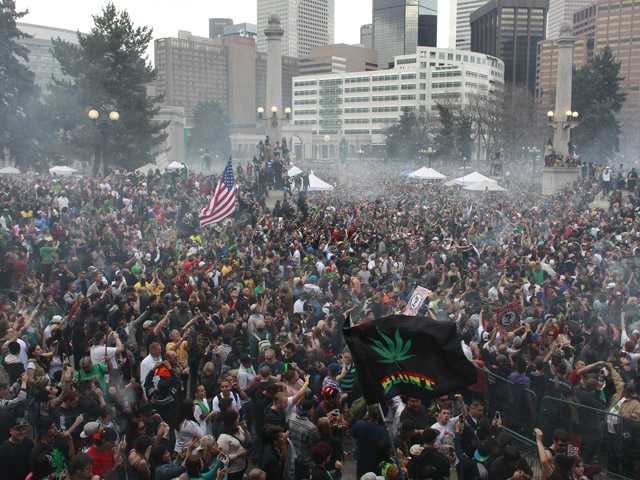 Members of a crowd numbering tens of thousands smoke marijuana simultaneously at 4:20 PM, at the Denver 420 pro-marijuana rally at Civic Center Park in Denver on Saturday. Even before the passage in November 2012 of Colorado Amendment 64 promised the legalization of marijuana for recreational use, April 20th has for years been a celebration of marijuana counterculture, and the 2013 rally draw larger crowds than previous years.
