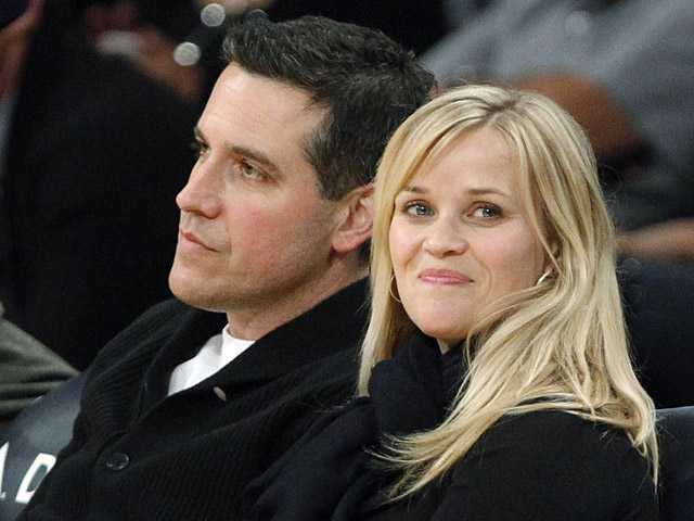 In this March 8, 2013 file photo, actress Reese Witherspoon and her husband, Jim Toth, watch the Toronto Raptors take on the Los Angeles Lakers in an NBA basketball game in Los Angeles.