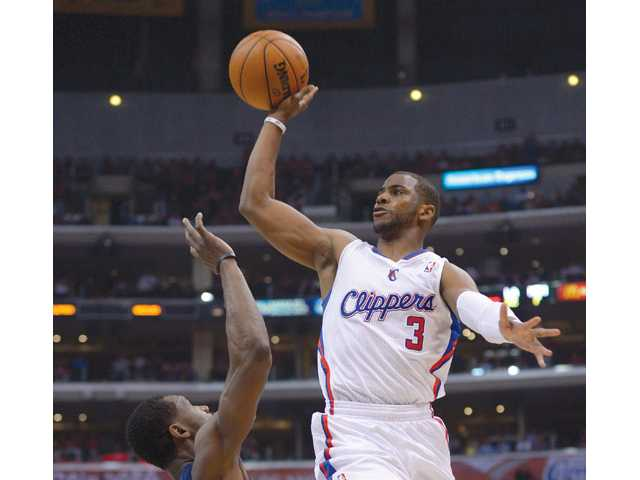 Los Angeles Clippers guard Chris Paul, right, shoots during a first-round NBA playoff series game on Monday in Los Angeles.