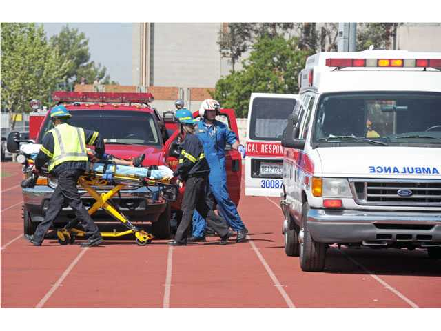 Emergency medical technicians transport an 8-year-old patient to a waiting Los Angeles County fire helicopter at Canyon High School's football field in Canyon Country on Tuesday. Signal photo by Jonathan Pobre