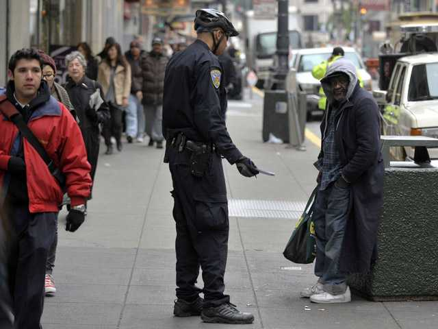 "In a Dec. 2009 file photo, San Francisco police officer Murray Daggs talks with a man who identified himself as ""James,"" a homeless panhandler in downtown San Francisco."