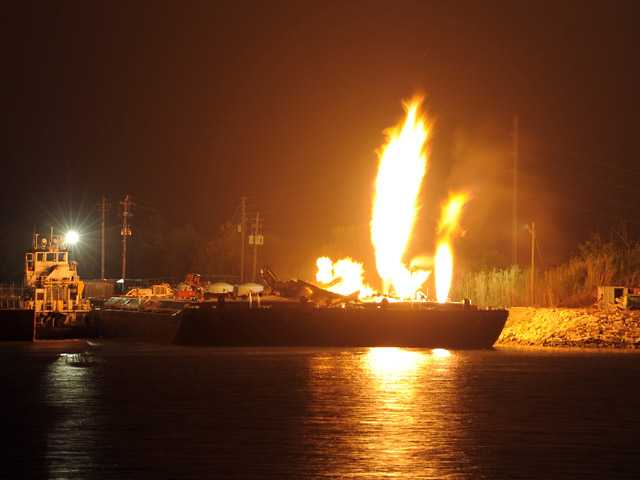 Fire burns aboard two fuel barges along the Mobile River after explosions sent three workers to the hospital Wednesday April 24, 2013. Fire officials have pulled units back from fighting the fire due to the explosions and no immediate threat to lives