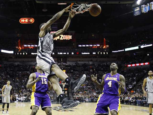 San Antonio Spurs' Kawhi Leonard (2) scores over Los Angeles Lakers' Antawn Jamison (4) and Metta World Peace (15).