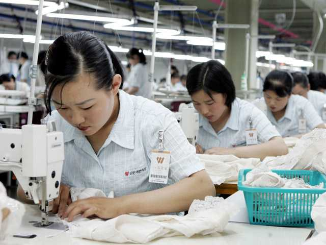 "In this June 2006 file photo, North Koreans work at a factory of South Korean apparel maker Shinwon company in the inter-Korean industrial park in Kaesong, North Korea. South Korea on Thursday warned of an unspecified ""grave measure"" if North Korea rejects talks on the jointly run factory park shuttered for nearly a month - setting up the possible end of the last remaining major symbol of inter-Korean cooperation."