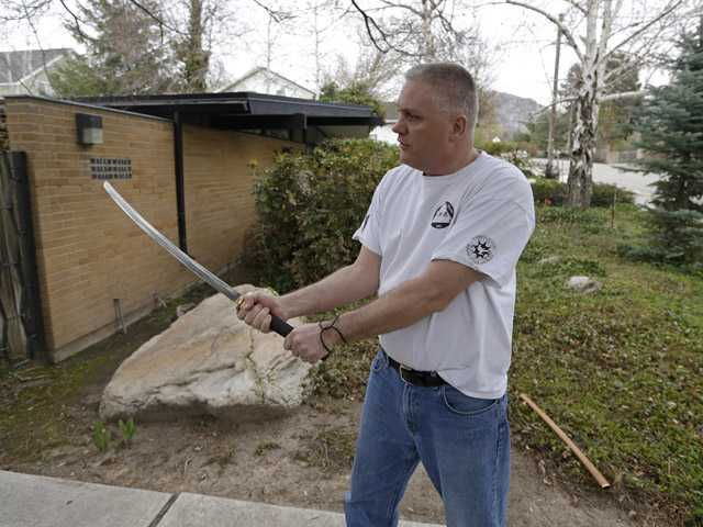 Kent Hendrix, 47, draws his sword near his house Tuesday in Salt Lake City. Hendrix, a Samurai sword-wielding Mormon bishop came to the aid of a woman who was being attacked in front of his house.