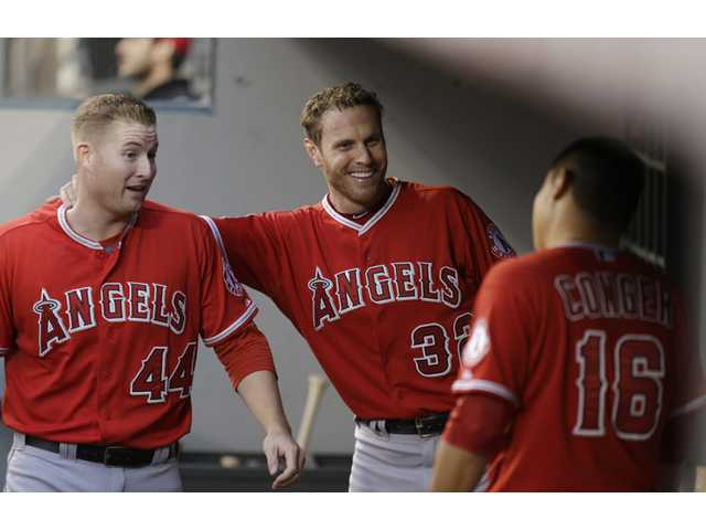 Los Angeles Angel Mark Trumbo, left, is greeted by teammates after hitting a two-run home run on Friday in Seattle.