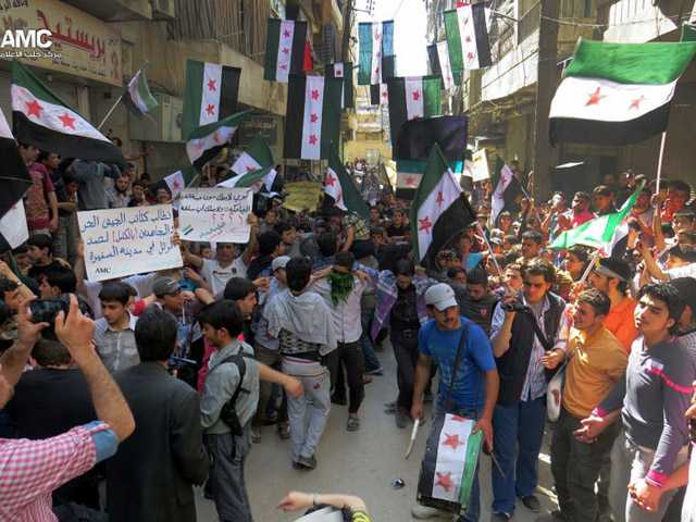 "This citizen journalism image provided by Aleppo Media Center AMC which has been authenticated based on its contents and other AP reporting, shows anti Syrian regime protesters holding banners and waving the Syrian revolutionary flags during a demonstration, in Aleppo, Syria, Friday, April 26, 2013. Araboc on banners read: ""we call upon the Free Syrian Army brigades and the Mujahedeen to stop the military convoy in the city of al-Safira,"" left, and ""all what Kerry has is the laughing cow cheese."""