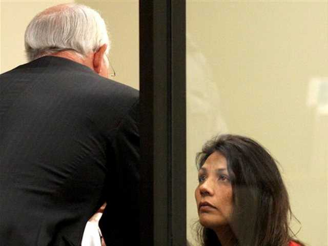 Nazila Sharaf listens to attorney Timothy Rien during her arraignment in Superior Court on felony and misdemeanor child abuse charges in Pleasanton, Calif., Thursday, April 25, 2013.