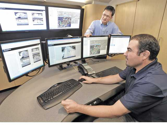 Santa Clarita Traffic engineer Andrew Yi, center, and Signal Operations Supervisor Cesar Romo, right, monitor traffic at City Hall. Signal photo by Dan Watson