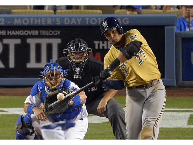 Milwaukee Brewers' Carlos Gomez, right, hits a two-run home run as Los Angeles Dodgers catcher A.J. Ellis, left, watches on Saturday in Los Angeles.
