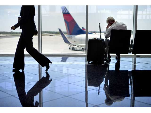 A passenger sits at right in the international terminal at Hartsfield-Jackson airport on Friday in Atlanta.
