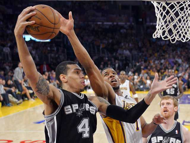 San Antonio Spurs guard Danny Green (4) grabs a rebound away from Los Angeles Lakers guard Darius Morris during the first half on Sunday in Los Angeles.