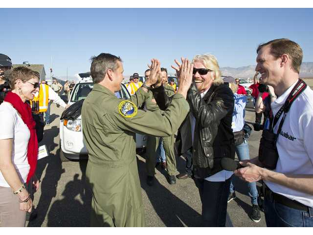Richard Branson, in dark jacket, and test pilot Mark Stucky after a successful test flight Monday morning.