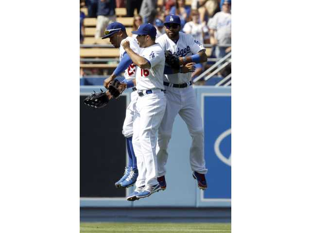 Los Angeles Dodgers left fielder Carl Crawford, left, right fielder Andre Ethier (16), and center fielder Matt Kemp, right, leap after defeating Milwaukee Brewers 2-0 during a baseball game Sunday in Los Angeles.