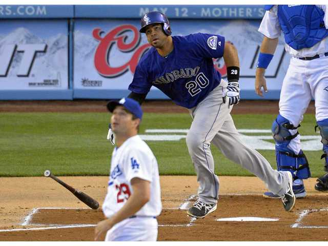 Colorado Rockies' Wilin Rosario, right, hits a home run as Los Angeles Dodgers pitcher Ted Lilly watches on Monday in Los Angeles.
