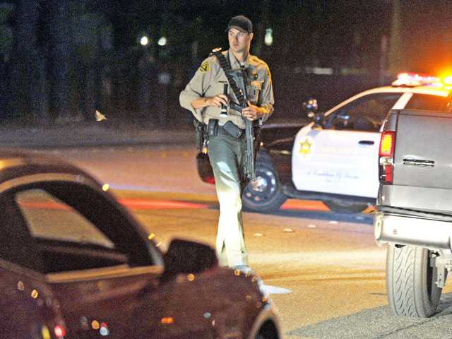 A sheriff's deputy diverts traffic on Sierra Highway after it is shut down to traffic at Adon Avenue in Canyon Country on Wednesday.