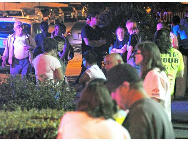 Residents wait at the La Pico Plaza shopping center at Soledad Canyon and Solamint roads as sheriff's deputies continue to search for a man nearby in Canyon Country on Wednesday.
