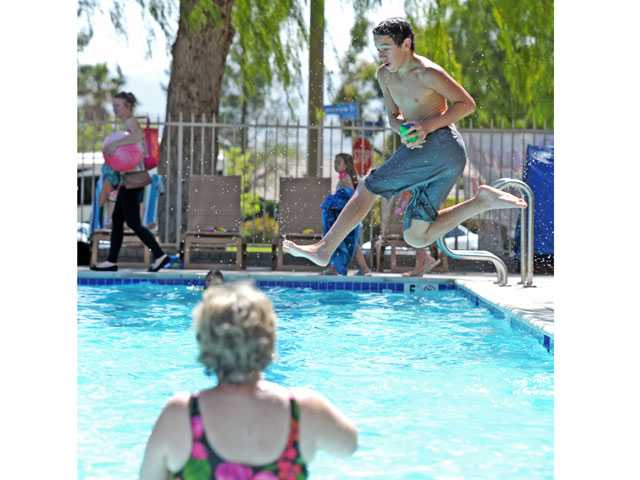 Ryan Harley, 13, catches a football thrown by his mother, Shelly Campbell-Harley, foreground, as he dives into a newly rapaired HOA pool in Northbridge. Signal photo by Jonathan Pobre