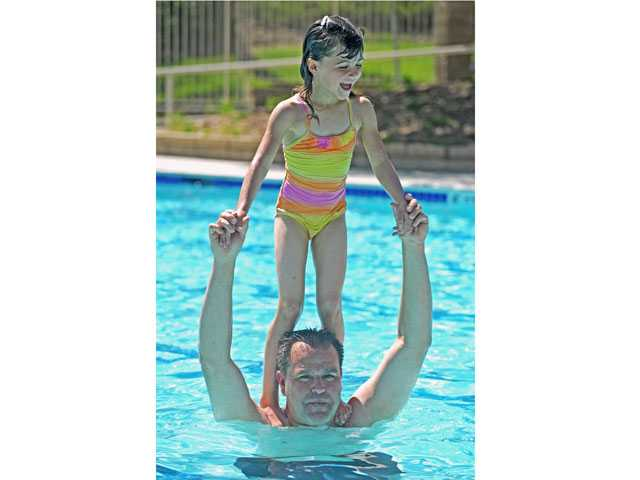 Summer Costello, 6, rides on Wolfgang Costello's shoulders in the newly repaired Northbridge HOA pool on Wednesday. Signal photo by Jonathan Pobre