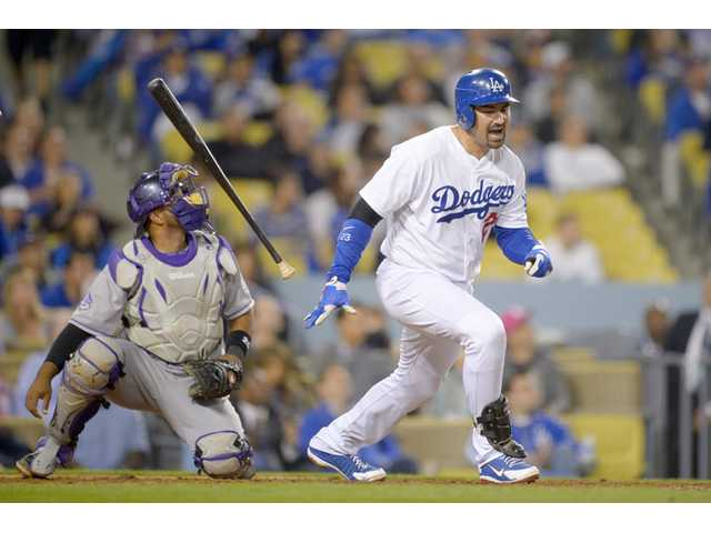 Los Angeles Dodger Adrian Gonzalez, right, throws his bat while Colorado Rockies catcher Wilin Rosario looks on Wednesday in Los Angeles.