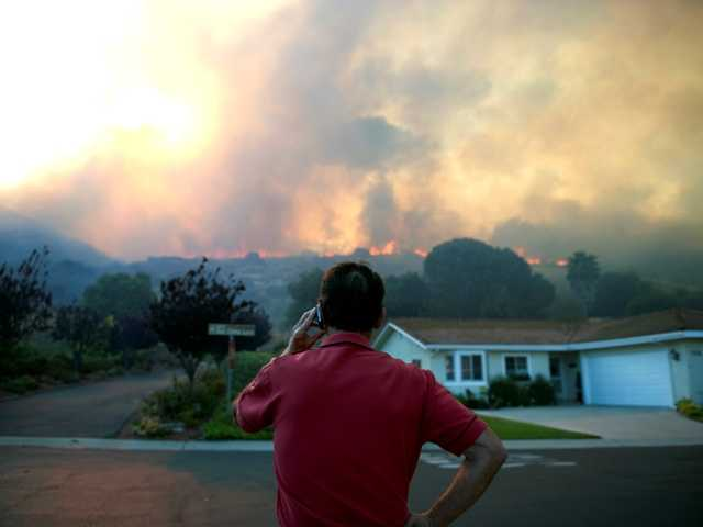 Reuben Ruiz makes a phone call as he watches the flames from a brush fire in Camarillo, Calif., Thursday, May 2, 2013.