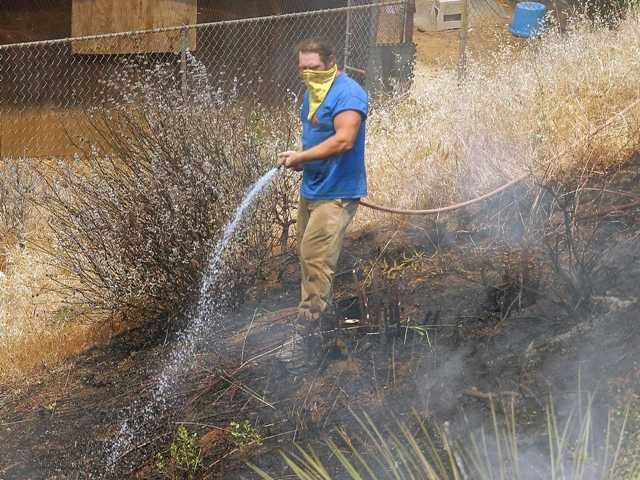 A resident waters the burned area next to his home in Point Mugu, Calif., Friday.