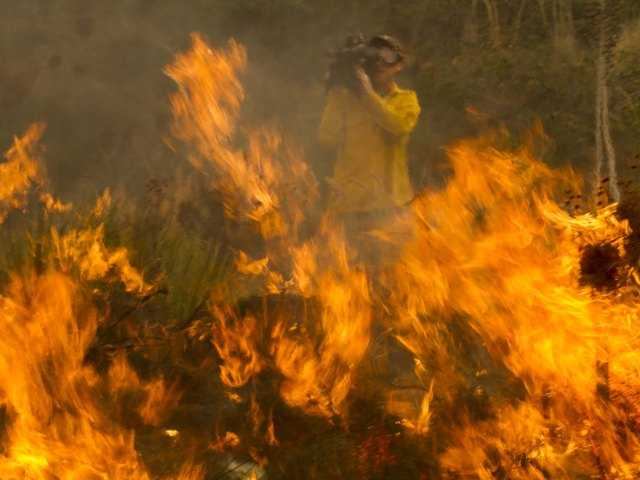 A cameraman records the wildfire burning along the Pacific Coast Highway near Ventura, Calif. on Friday.