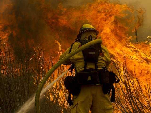 A firefighter battles the wildfire near the farmland along a hillside in Point Mugu , Calif. Friday