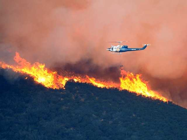 A water dropping helicopter gets ready to make a drop on a fire burring in Point Mugu State Park on Thursday.