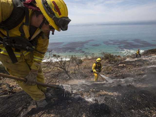 Fire burns down to the ocean at Point Mugu, Calif., on Friday.