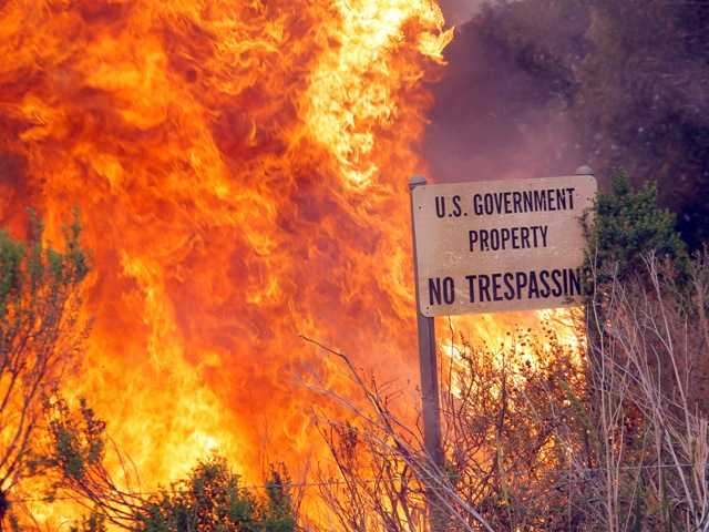 A brush fire burns a sign at the Naval Base Ventura County on Friday.
