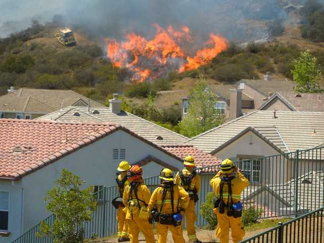 Firefighters from Glendale, Calif., and Pasadena watch as bulldozers clear a firebreak near homes in Thousand Oaks onThursday. A fire broke out in Glendale on Friday.